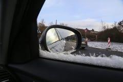 Winter snowy road in the car mirror. Winter snow-covered road in the mirror of the car stock image