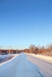 Winter snowy road in small town at sunny day Royalty Free Stock Photo