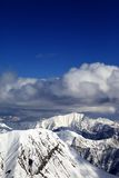 Winter snowy sunlit mountains and sky with clouds Stock Photography