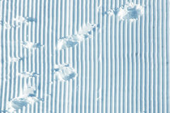 Winter snowy texture. Modified striped snow surface with human footprints, Bernese Alps, Switzerland Royalty Free Stock Image