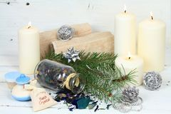 Winter spa concept with candles. Wellness objects, aromatic herbs, anti stress bath crystals and body cream on white wood table Royalty Free Stock Images