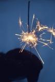 Winter sparkler. Blazing hand-held sparkler in winter Royalty Free Stock Photography