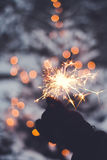 Winter sparkler. Blazing hand-held sparkler with snowy trees and blurred lights in the background Royalty Free Stock Photo