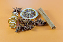 Winter spices for a festive occasion. With orange, star anise, stick cinnamon and coiled citrus peel on an orange background with copy space for your Christmas royalty free stock photography
