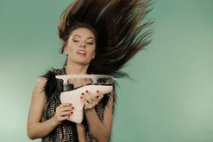 Woman with windblown hair holding ice skate Stock Photos