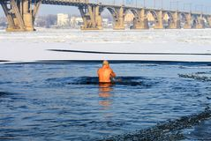 Winter sport. An elderly man swims in a winter river covered with ice during the Orthodox holiday Epiphany. Hardening royalty free stock photos
