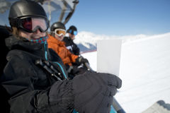 Winter sport friends in chair lift with ticket Royalty Free Stock Image