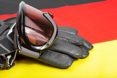 Winter sport goggles and gloves over German flag Stock Images