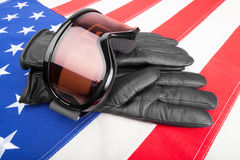 Winter sport goggles and gloves over US flag - studio shot Stock Photo
