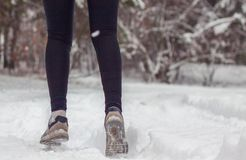Winter sport in the woods in the fresh air. Closeup of sneakers on the snow. stock photo