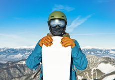 Winter sports concept - male snowboarder holding his snowboard before himself at the top of a mountain - outdoors shot. Winter sports concept - young male Royalty Free Stock Image