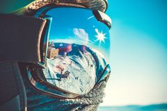 Winter sports concept - snowboarder in mask - outdoors shot. Winter sports concept - male snowboarder in snowboard mask at the top of a mountain - outdoors shot Stock Images