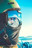 Winter sports concept - snowboarder his snowboard mask at the top of a mountain - outdoors shot. Winter sports concept - male snowboarder holding his snowboard Stock Photos