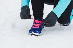 Tying sport shoes in snow. Winter sports fashion concept. Tying sport fitness shoes in snow, footwear for workout outside Royalty Free Stock Photo