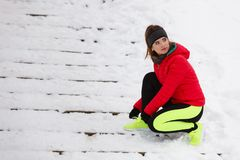 Woman tying sport shoes during winter. Winter sports fashion concept. Woman tying sport fitness shoes in snow, footwear for workout outside stock image