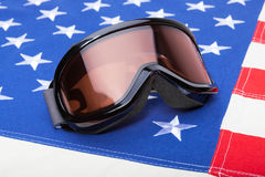 Winter sports implements over USA flag - snowboard or ski goggles Stock Photo