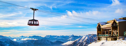 Winter sports travel background with cable car, mountain peaks. Winter sports travel vacation background. Cable car tram cabin, lift station, high snow mountain Stock Photo