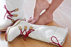 Winter sporty boots. White waterproof women winter sporty boots and female bare feet on hardwood floor Royalty Free Stock Photo