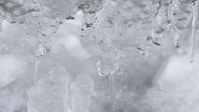 Winter or spring background icicles icy dripping flowing water melting ice looped video
