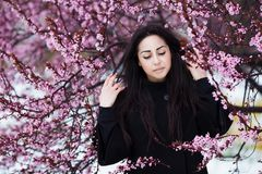 Winter, spring portrait of young beautiful brunette woman wearing warm coat. Flowers and snow beauty fashion concept Stock Photo