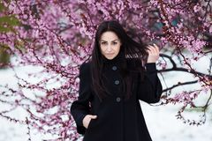 Winter, spring portrait of young beautiful brunette woman wearing warm coat. Flowers and snow beauty fashion concept Royalty Free Stock Photography