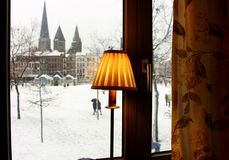 Winter square with snow view from window. Cozy interior with yellow lamp shade and curtains. Old buildings, castle and church landmark in Europe. Winter stock images