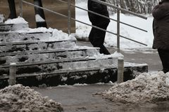 Winter. Stairs. People walk on a very snowy stairs to the underpass. People step on an icy stairs, slippery stairs.  royalty free stock photography
