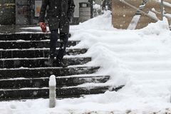 Winter. Stairs. People walk on a very snowy stairs. Uncleaned icy stairs in front the buildings, slippery stairs. royalty free stock images
