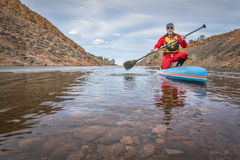 Winter stand up paddling in Colorado. Senior male paddler in drysuit is enjoying stand up paddling on lake in Colorado, winter scenery with some ice Royalty Free Stock Images