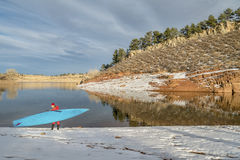 Winter stand up paddling in Colorado. Senior male paddler in drysuit and stand up paddleboard on lake in Colorado, winter scenery Stock Images