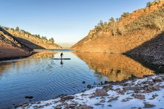 Winter stand up paddling in Colorado. Silhouette of a stand up paddler on a mountain lake in winter scenery - Horsetooth Reservoir in northern Colorado Stock Photo