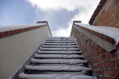 Winter steps. Some red brick stairs leading up, covered with snow, sunny cloudy sky Stock Photos