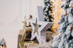 Winter still life with Christmas decorations toy deer, star and gift boxes on light background. soft focus, blurred Stock Photo