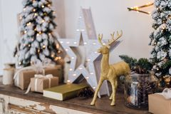 Winter still life with Christmas decorations toy deer, star and gift boxes on light background. soft focus, blurred. Background royalty free stock images