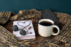 Winter still life with coffee, scarf and book on a wooden table. Winter still life with coffee, scarf, mittens, yarn and book on a wooden table Royalty Free Stock Photo