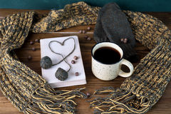 Winter still life with coffee, scarf and book on a wooden table Royalty Free Stock Photos