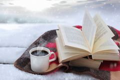 Winter still life: cup of coffee and opened book royalty free stock image