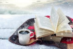 Winter still life: cup of coffee and opened book