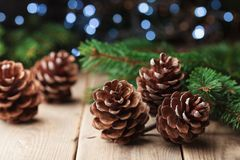 Winter still life with pine cones and fir tree on vintage wooden table. Holiday greeting card. Winter still life with pine cones and fir tree on wooden table royalty free stock images