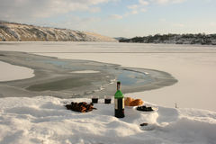 Winter still life on the river. Meat, wine, bread and olives on a background of a beautiful winter landscape Stock Image