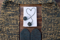 Winter still life with scarf, mittens and book on a wooden table Stock Photography