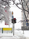Winter stoplight. Winter crossroads with traffic lights, snow drifts, road signs Royalty Free Stock Image