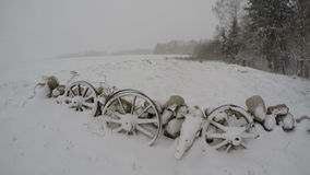 Winter storm in the fields, time lapse 4K. Snow falling on decorative stone wall with ancient horse carriage wooden wheels, time lapse 4K stock video footage