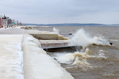 Winter storm on the lake and city embankment covered with ice Royalty Free Stock Photo