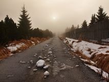 Winter stormy weather in mountains, dark snowy clouds, cold snow in the sky. The road covered by snow and ice. Slipper asphalt Stock Photos