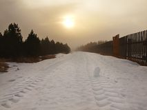 Winter stormy weather in mountains, dark snowy clouds, cold snow in the sky. The road covered by snow and ice. Slipper asphalt Stock Photo