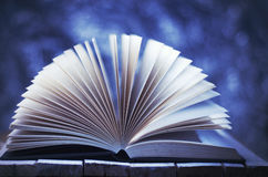 Winter story, book on blue vibrant background. Winter story, book on blue, vibrant, blurred background Stock Image