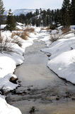 Winter stream. Winter snow bordered stream meanders through mountain community stock images