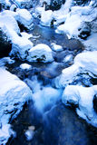 Winter stream. Scenery with cascading water over snow covered rocks Stock Photography