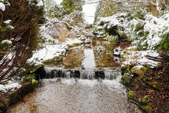 A narrow stream flows through a snow covered landscape and over a miniature waterfall. Stock Images